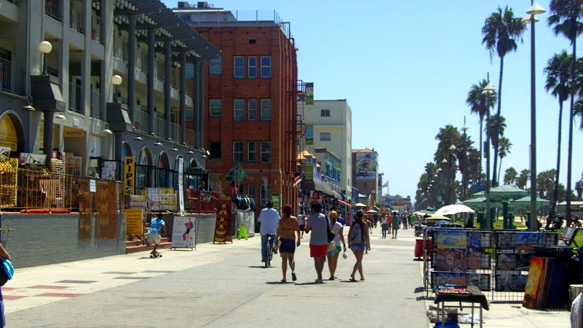 A shot looking down the Venice Beach Boardwalk with souvenir shops, historic buildings, palm trees and people walking.