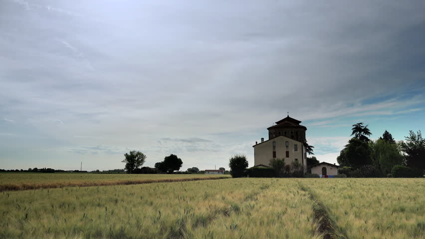 timelapse of wheat fields and church under cloudy sky in Italy #27544696