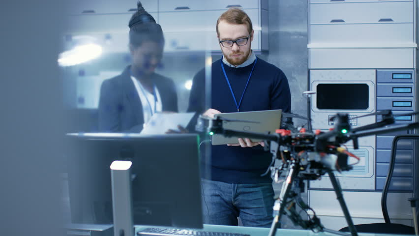 Caucasian Male and Black Female Engineers Working on a Drone Project with Help of Laptop and Taking Notes. He Works in a Bright Modern High-Tech Laboratory. Shot on RED EPIC-W 8K Helium Cinema Camera.