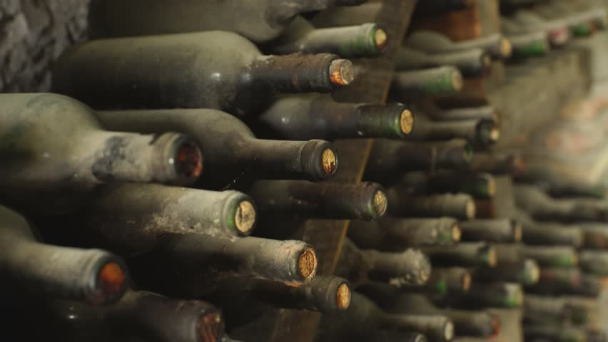 some very old and dusty wine bottles in a wine cellar