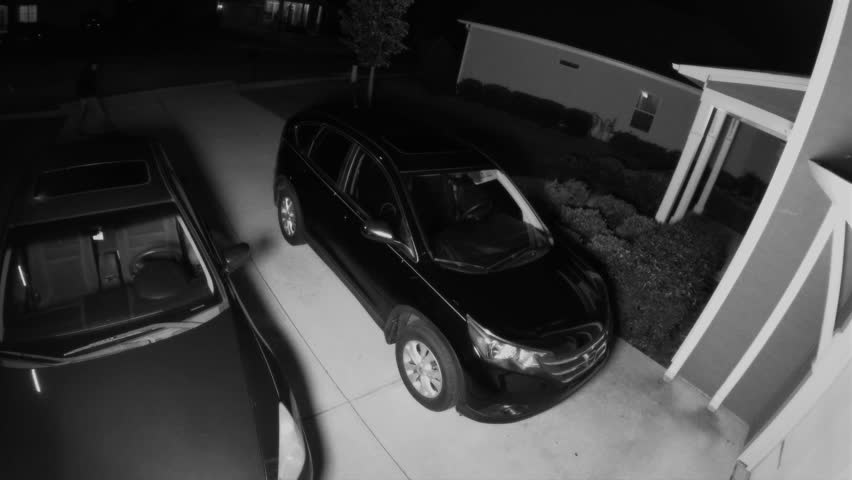 Night surveillance camera of a car thief breaking into a SUV and stealing a woman's purse in her neighborhood.