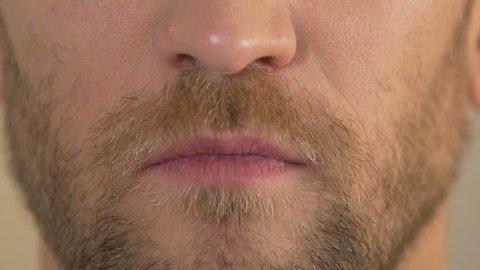 Close up of man's face smirking into camera, arrogant male, body language