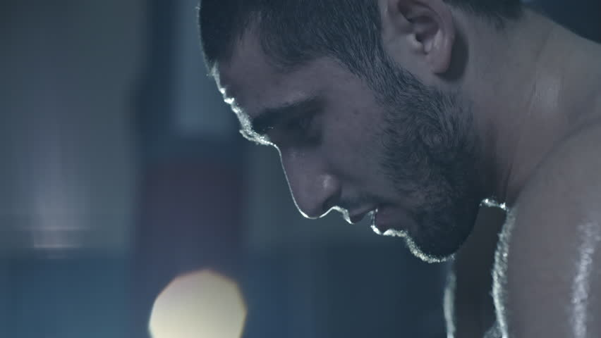Close up of devastated sweaty boxer resting and thinking in dark gym after losing fight