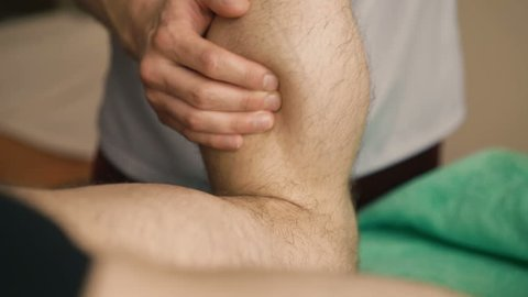 The masseur doing sports friction and massage of legs for sportsman