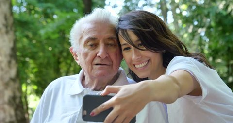 Granddaughter, a nurse, caring for the elderly, a girl (woman) and grandfather, do selfie, happy, smiles, in the park. Concept boarding house, sanatorium, house for the elderly, help for the elderly
