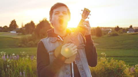 Hipster handsome man cheerful playing ukulele or small guitar at susnet