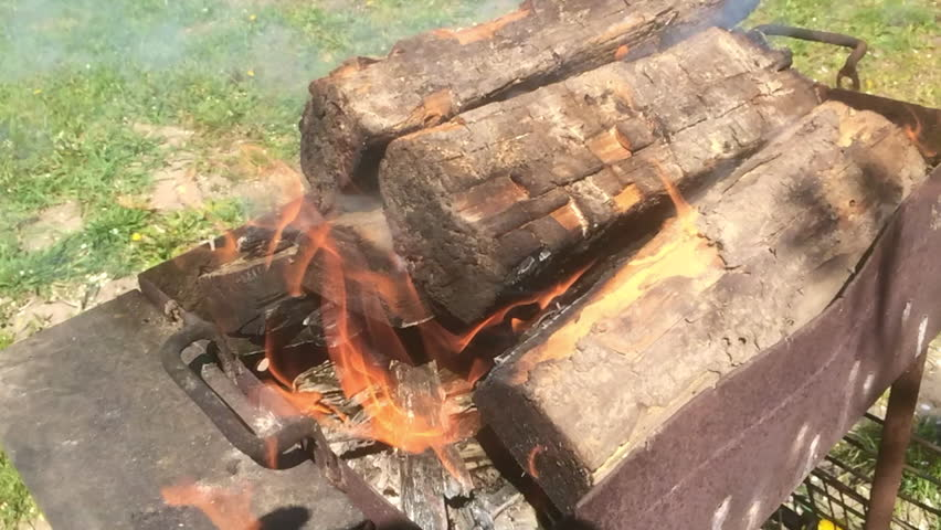 Video of fire brown wood dark grey black coals on bright yellow fire inside metal brazier. Wood burning in the braziers. Flames fires preparation for cooking barbecue. Brazier of nature bbq background #27628417
