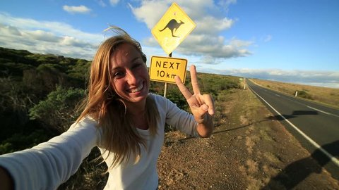 Young woman traveling takes selfie with kangaroo crossing sign Cheering young woman takes a selfie portrait on the road standing next to a kangaroo warning sign, Australia.