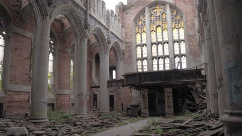 CLOSE UP: Exploring stunning crumbling nave in abandoned City Methodist Church, USA. Old religious building collapsing. Ruined pillars, graffiti on the walls, shuttered windows in decaying cathedral
