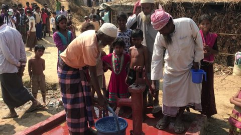 TEKNAF, BANGLADESH - APRIL 1, 2017 : Some Rohingya people pumping water out of the well pipe in refugee camps Kutupalong Rohingya near Cox's Bazar, Bangladesh.