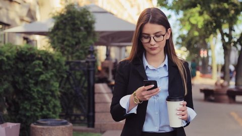 Young business woman is walking on the street and drinks coffee and using smartphone at lunch break.