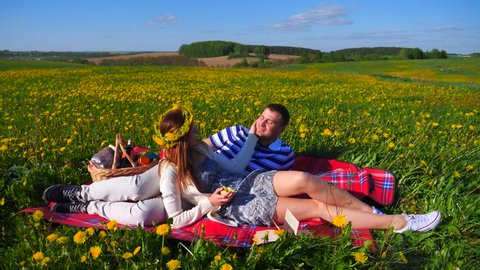 Happy couple in love sitting on a picnic in a field of yellow flowers of dandelions, gently stroking a hand across his face and kisser.