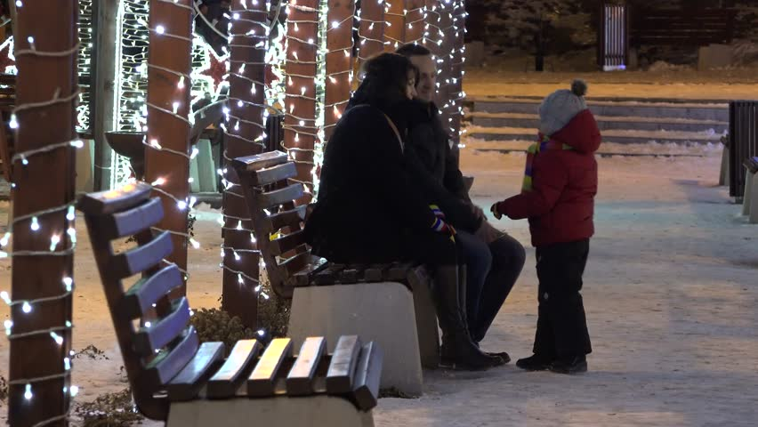 Young parents and little child in the winter park, Christmas light, happy time | Shutterstock HD Video #27705382