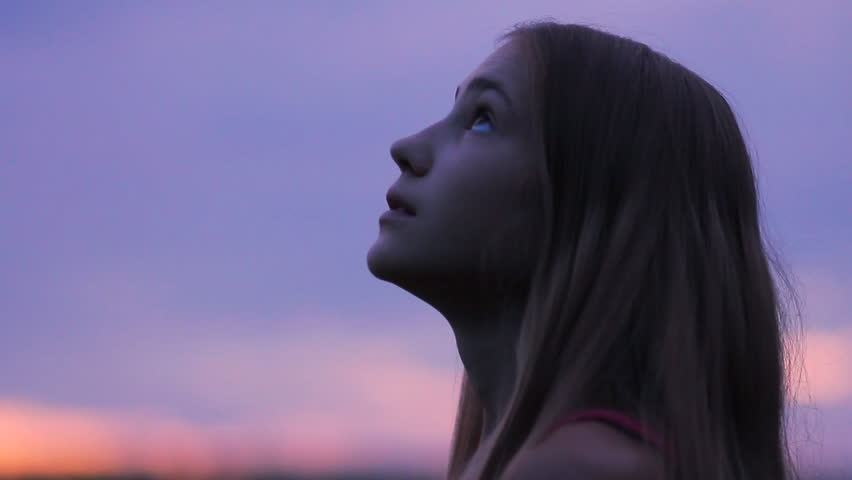 Beautiful girl praying looking up at purple sky with hope, close-up. Silhouette of young woman dreaming looking upwards sunset outdoors.  | Shutterstock Video #27705571