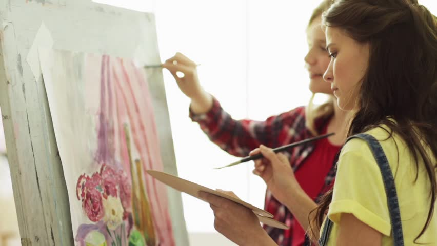 art school, creativity and people concept - student girls or friends with easel, paintbrushes and palettes painting still life at studio