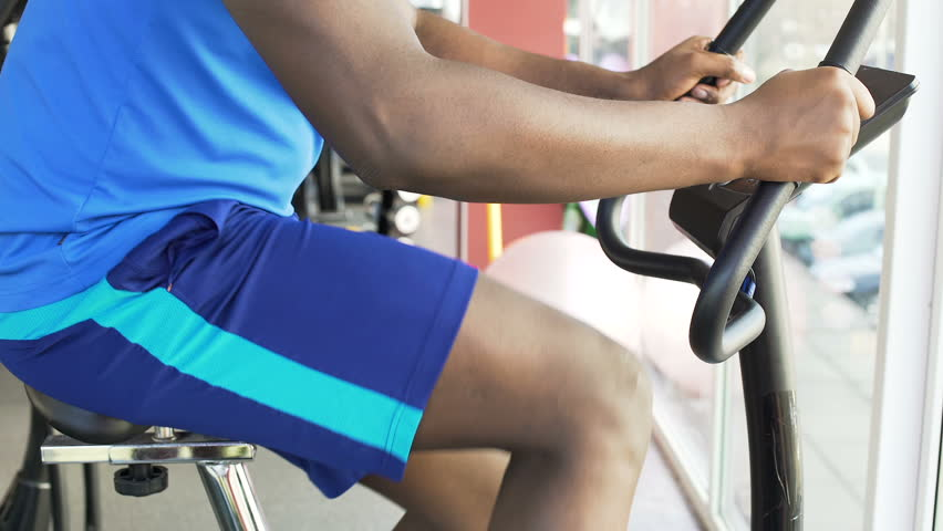 Purposeful Afro-American man riding an exercise bike in the fitness club, sport | Shutterstock HD Video #27742972