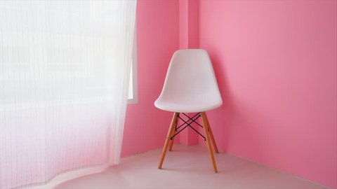 Movement of white curtain in modern room, decoration with white chair and pink wall.