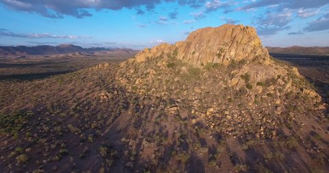 Aerial drone video of large rock formation south of capital Windhoek and railway line area in African savanna landscape in dry season in central highland Khomas Hochland of Namibia, southern Africa