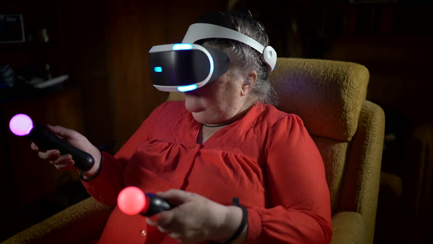 Elderly woman in VR headset uses move motion controller for video game console. 70 year old woman playing virtual reality game in front of TV screen at home.