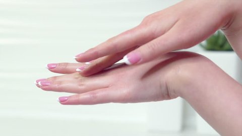 Beautiful Woman applying moisturizing cream on her Hands. Spa and Manicure concept. Female hands with french manicure. Soft skin, skincare concept. Beauty nails. Slow motion 4K UHD video