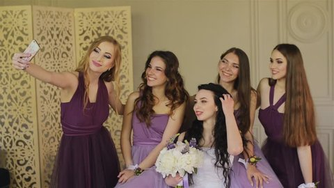 Bridesmaids taking a selfie on a smartphone and laugh during the morning of the bride in a beautiful photo studio. Beautiful girls in purple wedding dresses have fun in the studio.