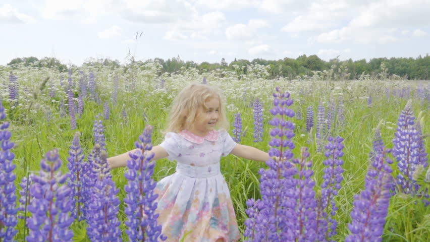 Cute Little Having Fun And Spinning In The Field Among Flowers Of Lupine