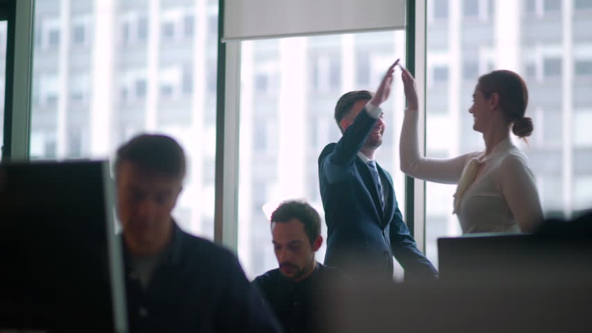 Business High Five - Office worker high five's a colleague as they walk passed people sitting at their desk.