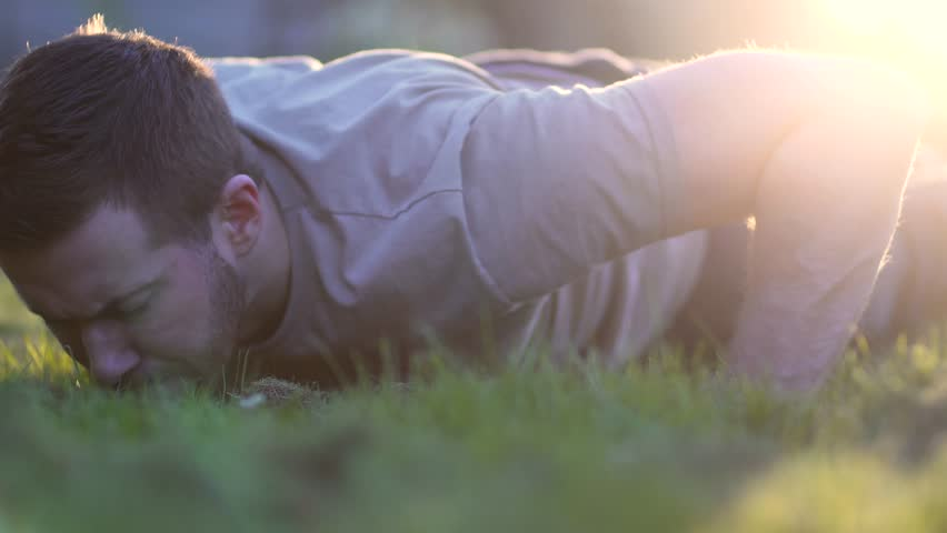 Young man doing clap push-ups outdoors for a workout  or army military training. Handsome White Caucasian. Fitness and hard exercise in 4K at sunset.