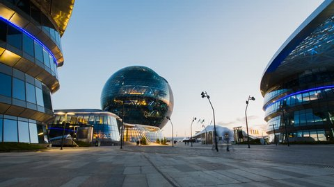 ASTANA, Kazakhstan - June 10, 2017: Timelapse of modern sphere building of EXPO with people moving around on sunset