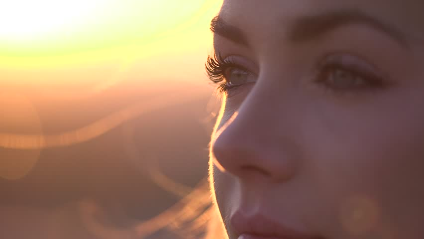 Closeup of woman's face outside at sunrise/sunset. Wide shot, slow motion, handheld