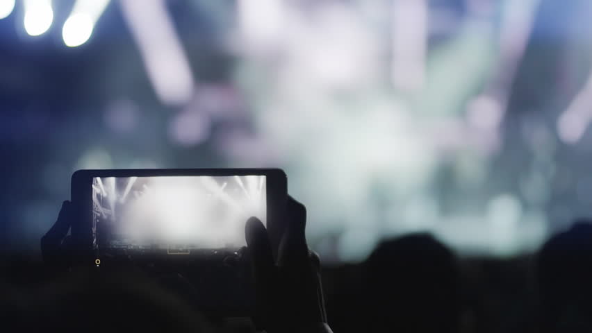 Recording a night music concert with cellphone or tablet 100p.An outdoor summer night rock concert.Front row crowd people record video of the concert woth a cell phone or tablet.
