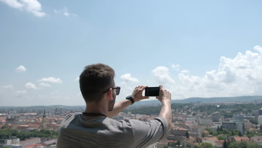 Male traveller make a panoramic photo of the old city to his phone for Instagram or other social networks. Travel to Romania. | Shutterstock HD Video #27841432