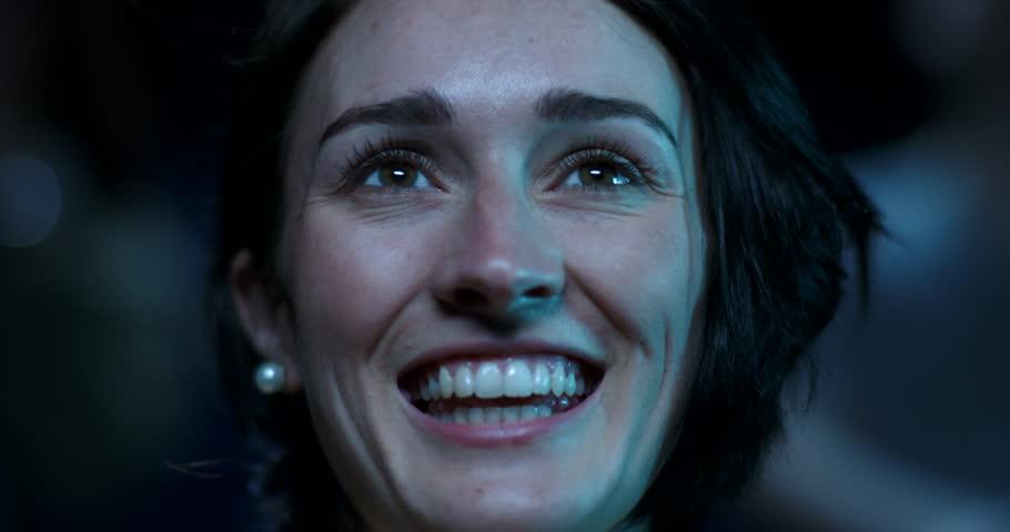A young woman at the movies begins to smile and laugh