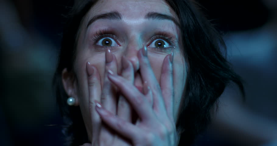 Close up of a scared young woman using her hands to cover her face while watching a scary movie.