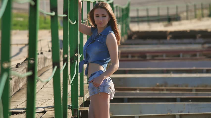 Beautiful sexy girl is standing on a bridge shorts and jeans shirt lifestyle