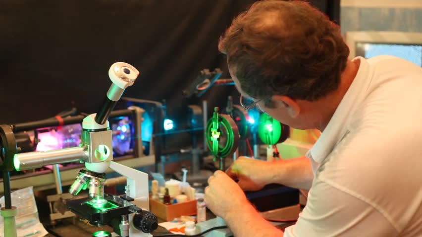 scientist adjust device consisting of laser, microscope and enlargers close up
