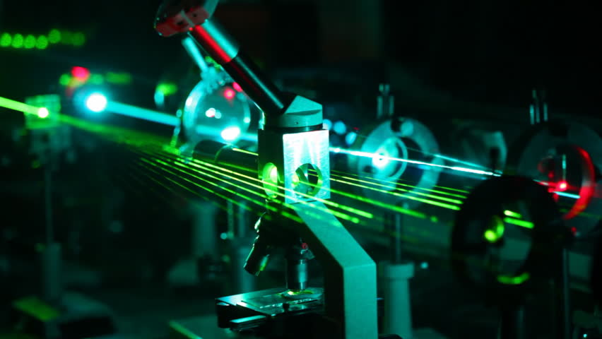 microscope and multi-colored lasers passing in it in dark close up