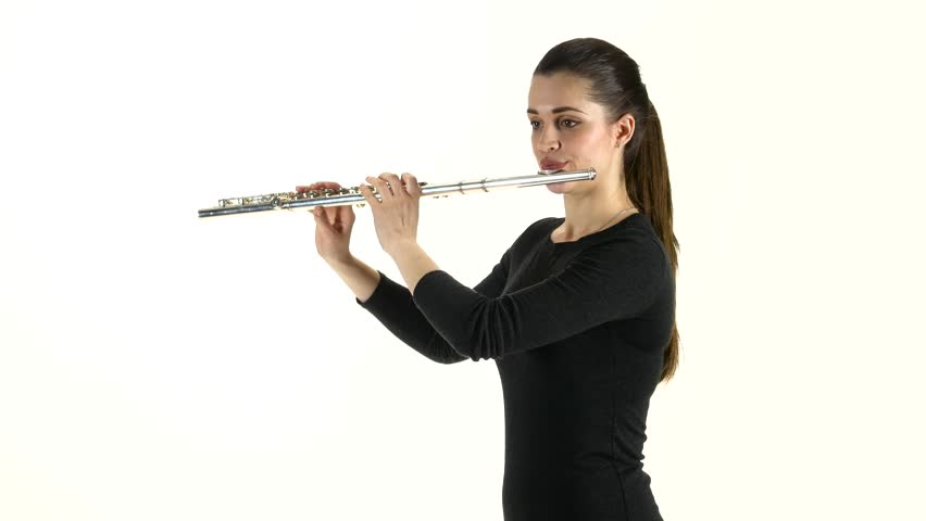 Girl musician playing on flute standing sideways on white background