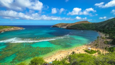 Aerial view time lapse with moving clouds above the beach with coral reef in famous Hanauma Bay Nature Preserve, Oahu island, Hawaii, United States. Summer time leisure and water sports recreation.