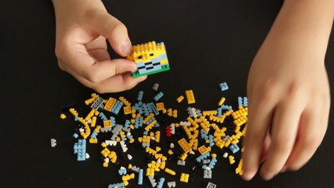 Child's hands playing with a small lego bricks, Hands Close Up. Lego is a popular line of construction toys. Top view.