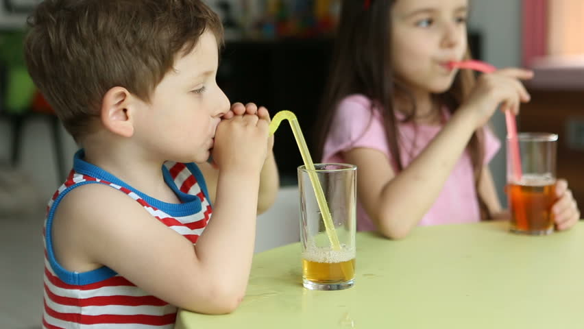 Funny small boy making bubbles in glass with juice. Happy kids. Two children sitting at the table. Video footage