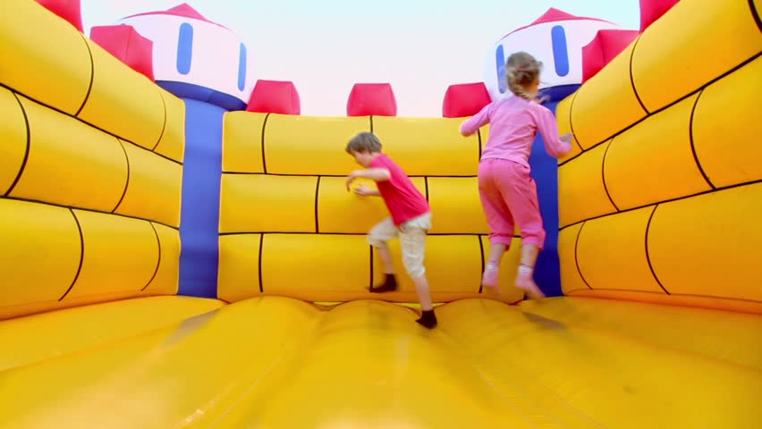Pair of children boy and little girl jump at inflatable playground at sunny summer day