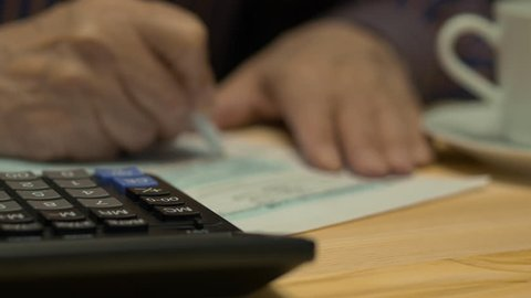 An Elderly Man Is Completing The Us Individual Income Tax Return Form 1040. Fake sensitive information (credit card, bank account, medical information, signature)