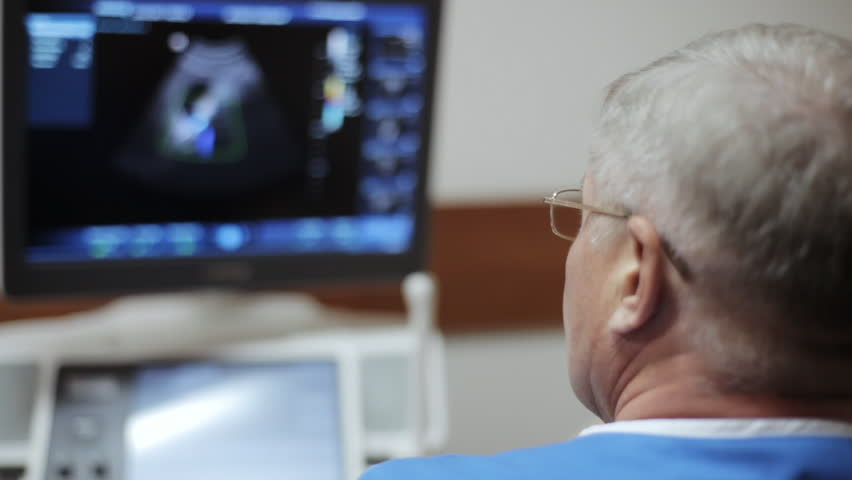 Male doctor taking a sonogram of abdomen and looking on the screen ultrasound device the hospital. Focus on the doctor's glasses and blured screen on the background.