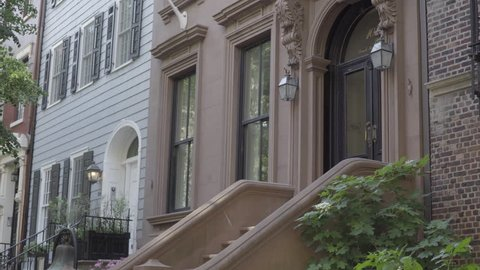 Exterior establishing 4K video shot of typical Brooklyn style brownstone facade. Man walks up famous architecture steps to front door