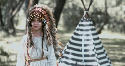 Little girl playing in a teepee tent outdoors, wearing Indian headdress, pretending to be a native American. 4K UHD RAW edited footage