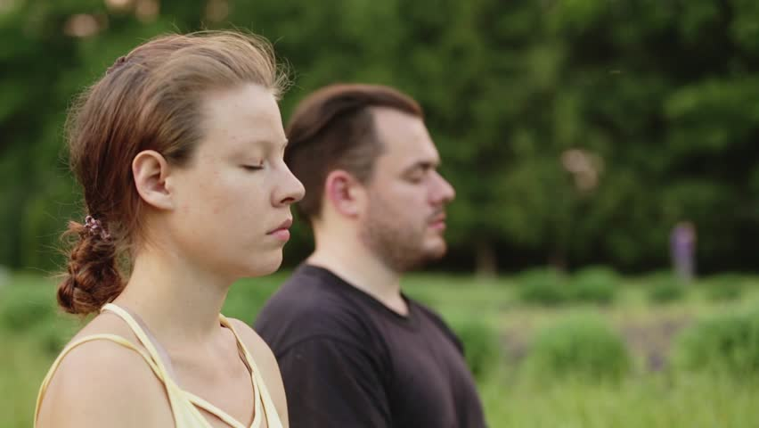 A man and a woman meditate in bliss. Young yoga instructors practice in a city park on green grass. Successful young people perform acro yoga exercises. Close up shot. Focus on woman.