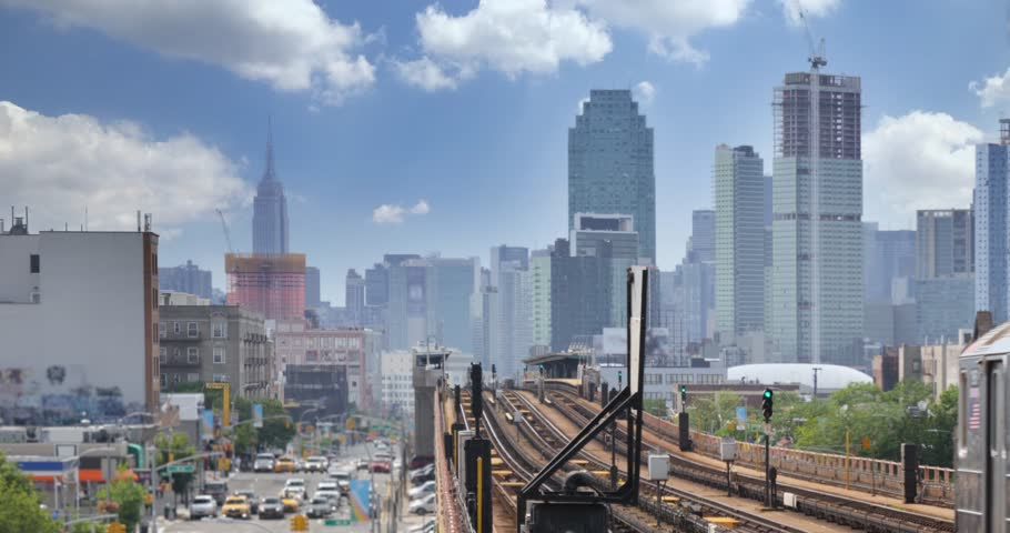 A view of the Manhattan skyline as seen from an elevated subway platform over Queens Boulevard in Queens.  Empire State Building in the distance.