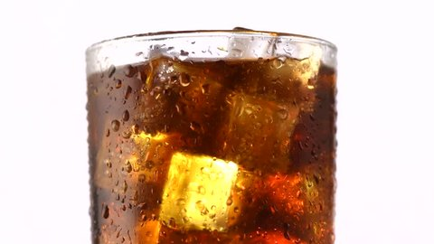 Cola with ice cubes background. Cola drink with Ice and bubbles and water drops on glass. Soda closeup. White background. Rotation Fizzy drink. 4K UHD video footage. Ultra high definition 3840X2160