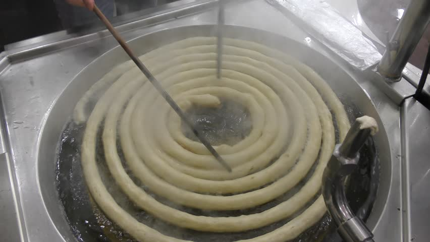 Timelapse: Frying Churros in deep oil in churreria, traditional dough pastry snack. Churros are popular mostly in Spain, dipped in champurrado, hot chocolate, dulce de leche or cafe con leche.